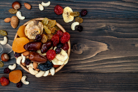 Photo for Mix of dried fruits and nuts on a dark wood background with copy space. Top view. Symbols of judaic holiday Tu Bishvat - Royalty Free Image