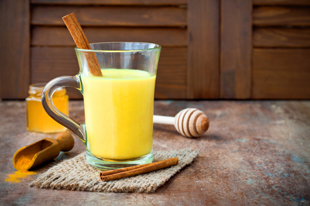 Photo pour Turmeric golden milk latte with cinnamon sticks and honey. Detox liver fat burner, immune boosting, anti inflammatory healthy cozy drink. Copy space - image libre de droit