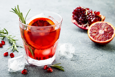 Foto de Red cocktail with blood orange and pomegranate. Refreshing summer drink on gray stone or concrete background - Imagen libre de derechos
