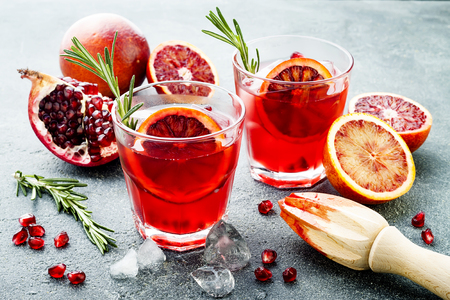 Foto de Red cocktail with blood orange and pomegranate. Refreshing summer drink on a gray stone or concrete background. Holiday aperitif for Christmas party. - Imagen libre de derechos