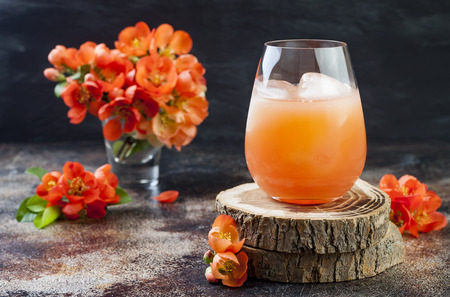 Photo for Floral pastel peach and pink brunch cocktail garnished with quince flowers over old rustic background. - Royalty Free Image