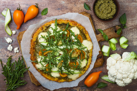 Foto de Cauliflower pizza crust with pesto, yellow tomatoes, zucchini, mozzarella cheese and squash blossom. - Imagen libre de derechos