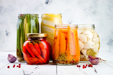 Photo for Marinated pickles variety preserving jars. Homemade green beans, squash, cauliflower, carrots, red chili peppers pickles. Fermented food. - Royalty Free Image