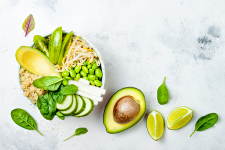 Photo pour Vegan, detox green Buddha bowl recipe with quinoa, avocado, cucumber, spinach, tomatoes, mung bean sprouts, edamame beans, daikon radish. Top view, flat lay, copy space - image libre de droit