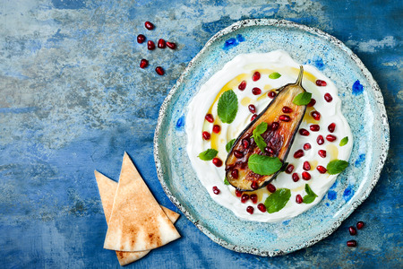 Photo pour Labneh middle eastern lebanese cream cheese dip with roasted aubergine, pomegranate, mint and pita. Top view, overhead, copy space - image libre de droit