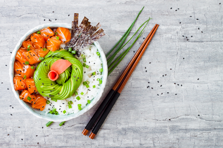 Photo for Hawaiian salmon poke bowl with seaweed, avocado rose, sesame seeds and scallions. Top view, overhead, flat lay, copy space - Royalty Free Image