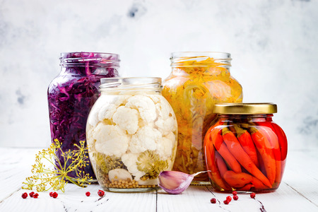 Photo for Sauerkraut variety preserving jars. Homemade red cabbage beetroot kraut, turmeric yellow kraut, marinated cauliflower, red chili peppers pickles. Fermented food. - Royalty Free Image