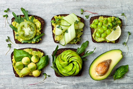 Photo for Fresh avocado toasts with different toppings. Healthy vegetarian breakfast with rye wholegrain sandwiches  - Royalty Free Image