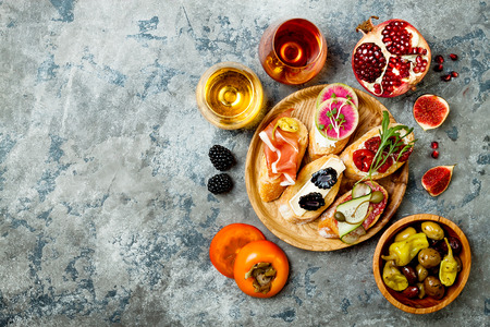 Photo for Appetizers table with italian antipasti snacks and wine in glasses. Brushetta or authentic traditional spanish tapas set, cheese variety board over grey concrete background. Top view, flat lay, copy space - Royalty Free Image