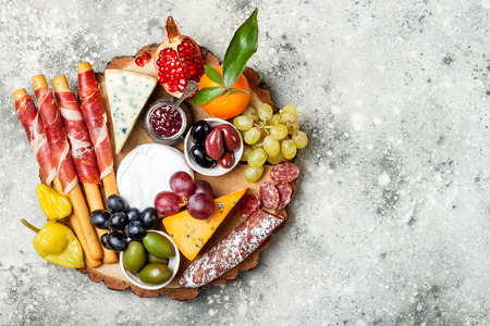 Photo pour Appetizers table with antipasti snacks. Cheese and meat variety board over grey concrete background. Top view, flat lay, copy space - image libre de droit