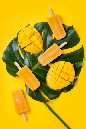 Foto de Mango popsicles over green tropical palm leaf on yellow colored background. Minimal flat lay style. Overhead, top view - Imagen libre de derechos