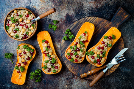 Photo for Stuffed butternut squash with chickpeas, cranberries, quinoa cooked in nutmeg, cloves, cinnamon. Thanksgiving dinner recipe. Vegan healthy seasonal fall or autumn food - Royalty Free Image