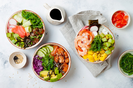Photo pour Hawaiian salmon, tuna and shrimp poke bowls with seaweed, avocado, mango, pickled ginger, sesame seeds. Top view, overhead, flat lay - image libre de droit