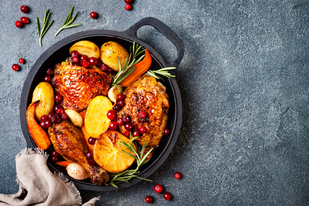 Photo pour Roasted chicken legs with root vegetables, lemon, garlic, cranberry and rosemary on pan, on black slate stone background - image libre de droit