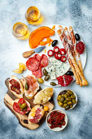 Photo pour Appetizers table with antipasti snacks and wine in glasses. - image libre de droit