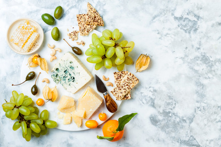 Photo pour Cheese platter with different cheeses, grapes, nuts, honey. - image libre de droit