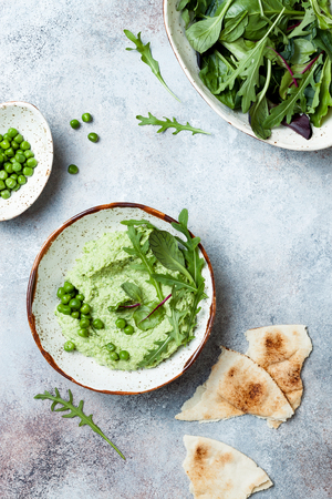 Foto per Green pea hummus spread or dip with mix salad leaves. Healthy raw summer appetizer, vegan, vegetarian snack. - Immagine Royalty Free
