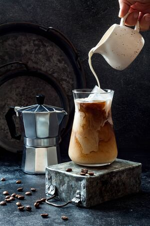 Foto de Cold refreshing iced coffee in a tall glass and coffee beans on dark background. Pouring cream into glass with iced coffee - Imagen libre de derechos