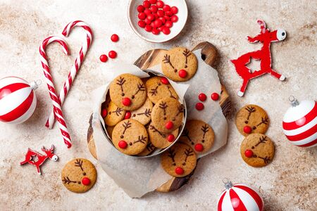 Foto de Cooking Christmas gingerbread. Decorated red nosed reindeer cookies with chocolate buttons and melted chocolate. Festive homemade decorated sweets - Imagen libre de derechos