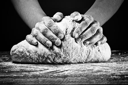 Foto de Woman's hands kneading the dough. In black and white style on dark background. - Imagen libre de derechos