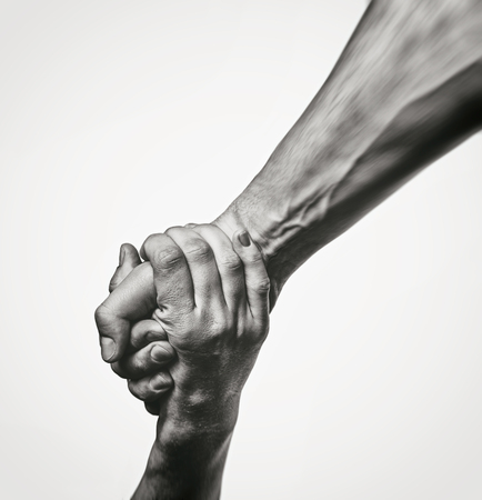 Foto de Concept of salvation. Black and white image of the hands of two people at the time of rescue (help). - Imagen libre de derechos