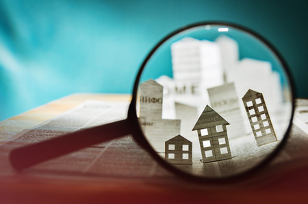 Photo for Magnifying glass in front of an open newspaper with paper houses. Concept of rent, search, purchase real estate. - Royalty Free Image