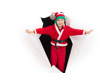 Foto de Child Santa Claus comes out of a hole in paper. A boy in a New Years costume is smiling. Holiday surprise. Christmas holiday concept - Imagen libre de derechos