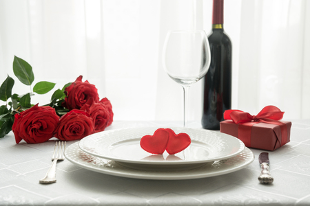 Foto de Valentines day table place setting with red roses, gift box, and wine. Space for text. Invitation for a date. - Imagen libre de derechos
