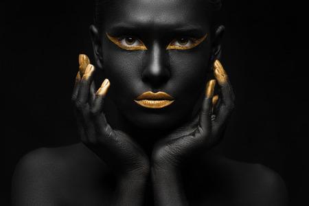 Photo pour black background and black woman with chic gold makeup - image libre de droit