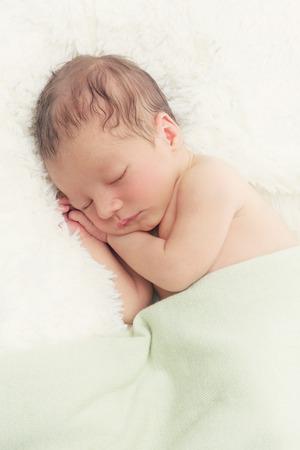 Photo pour Adorable sleeping newborn baby boy with hands under head. Copy space. Vertical composition. - image libre de droit