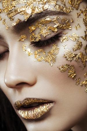 Photo pour Closeup portrait of beautiful young woman with golden foil on face and lips. Creative makeup. Long hair - image libre de droit