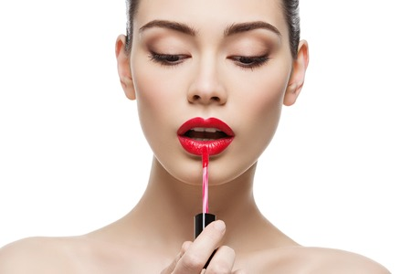 Photo for Beautiful young woman applying red lipgloss with applicator. Isolated over white background. Copy space. - Royalty Free Image