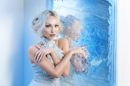 Foto de Beautiful young woman in crown and silver top standing near frozen mirror. Snow queen. Copy space. - Imagen libre de derechos