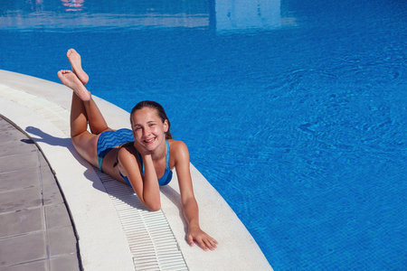 Photo for teen girl relaxing near swimming pool - Royalty Free Image