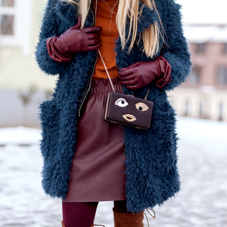 Foto de Street and bright style. A young girl in a fur coat, a stylish leather skirt. A fun bag. Details. Sguare image photo - Imagen libre de derechos