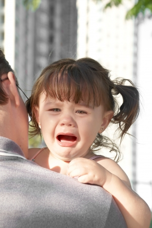 young girl crying on her father
