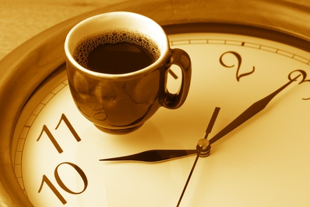 Coffee time: cup of coffee on clock dial. Monochrome toned image.
