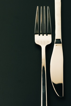 Close-up of fork and knife on dark background with copy space.