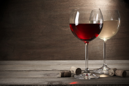 Foto de Glasses of red and white wine with corks on rustic wooden background with copy space. - Imagen libre de derechos