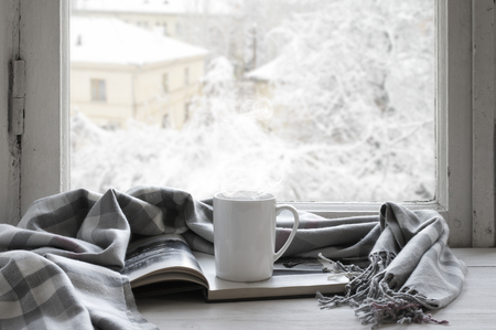 Foto de Cozy winter still life: mug of hot tea and opened book with warm plaid on vintage windowsill against snow landscape from outside. - Imagen libre de derechos