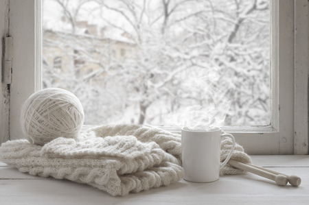 Foto de Cozy winter still life: mug of hot tea and warm woolen knitting on vintage windowsill against snow landscape from outside. - Imagen libre de derechos