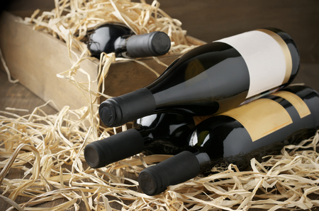 Photo pour Assorted closed wine bottles lying on straw and vintage wooden box. - image libre de droit
