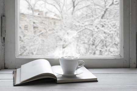 Foto de Cozy winter still life: cup of hot coffee and opened book on vintage windowsill against snow landscape from outside. - Imagen libre de derechos