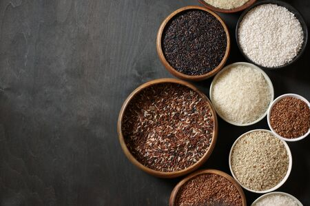 Photo for Set of various rice in bowls: white glutinous, black, basmati, brown and thai red mixed rice. Black wooden background, low light, top view. - Royalty Free Image