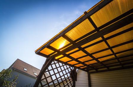 Foto de The roof of the veranda of orange polycarbonate on blue sky background. - Imagen libre de derechos