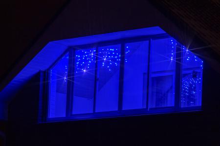Foto de Christmas blue garland adorns the balcony of a private house. - Imagen libre de derechos