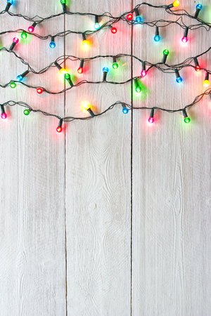 Photo for Christmas lights over white painted planks for background - Royalty Free Image