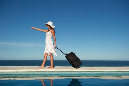 Traveler with heavy baggage walking on a swimming pool with sea view in Arraial d\'Ajuda, Bahia, Brazil