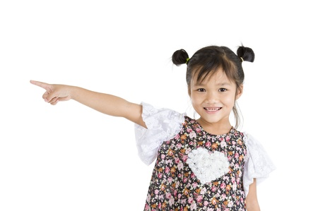 smiling little girl pointing to the side, isolated on white background