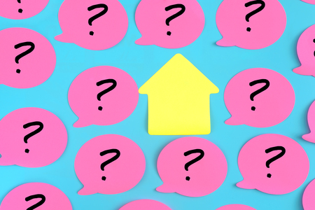 Photo pour Pink stickers with question marks drawn on them on a blue background. In the center there is an empty yellow sticky piece in the form of a house. Photo from the top. - image libre de droit